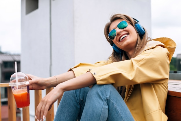 Autumn portrait of stylish happy woman listening music and ready to have her take away lunch