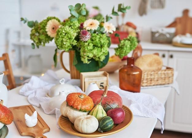 Осенняя открытка. день благодарения. хэллоуин. белая кухня с тыквами и цветами. фон урожая