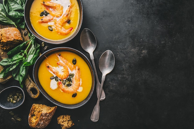 Autumn pumpkin creamy soup in bowls