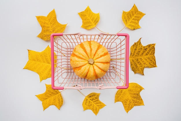 Autumn pumpkin in food basket and fall leaves on white