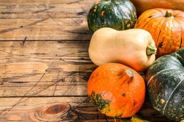 ハロウィーンの秋のカボチャフレームはオレンジ色です。木製の背景。上面図。スペースをコピーします。