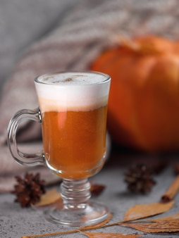 Autumn pumpkin latte glass. a warming drink and a knitted scarf on the gray table.