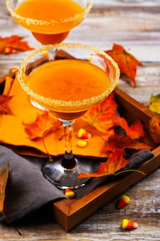 Autumn pumpkin martini cocktail with fall leaves on wooden tray
