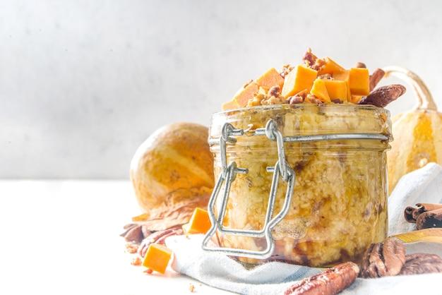 가을 호박 피칸 오트밀, 버터넛 스쿼시 조각, 피칸 너트, 카라멜 소스를 곁들인 밤새 귀리 죽, 흰색 나무 배경 복사 공간