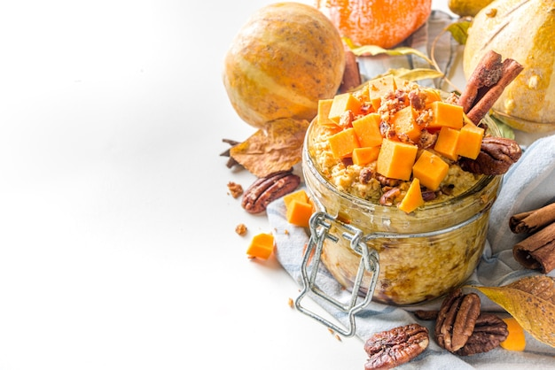 Autumn pumpkin pecan oatmeal, overnight oats porridge with butternut squash slices, pecan nuts and caramel sauce, white wooden background copy space