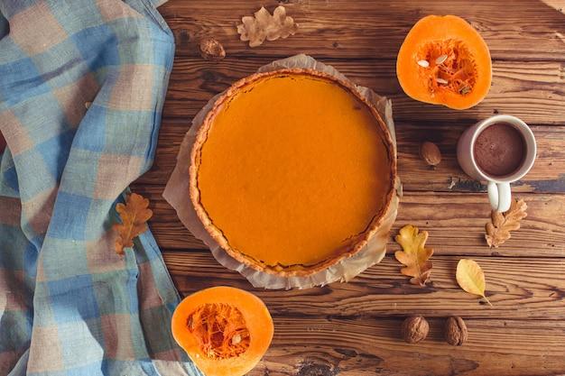 Autumn pumpkin pie shortcrust tart with orange pumpkin cream on brown wooden background