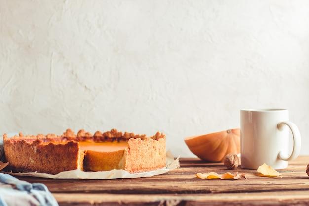 흰색 콘크리트 배경에 주황색 호박 크림을 곁들인 가을 호박 파이 shortcrust 타르트