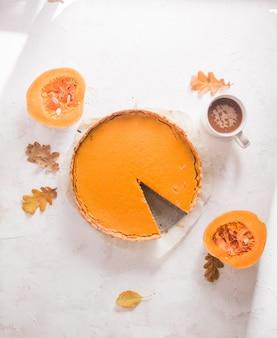 Autumn pumpkin pie shortcrust tart with orange pumpkin cream on white concrete background