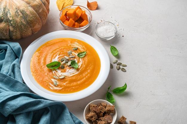Осенний тыквенный суп в белой тарелке на сером фоне с тыквенными специями и ржаными сухариками