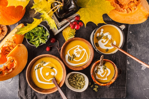 Autumn pumpkin soup puree with cream in cups, the autumn scenery. healthy vegan food concept.