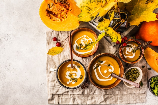 Autumn pumpkin soup puree with cream in cups, the autumn scenery