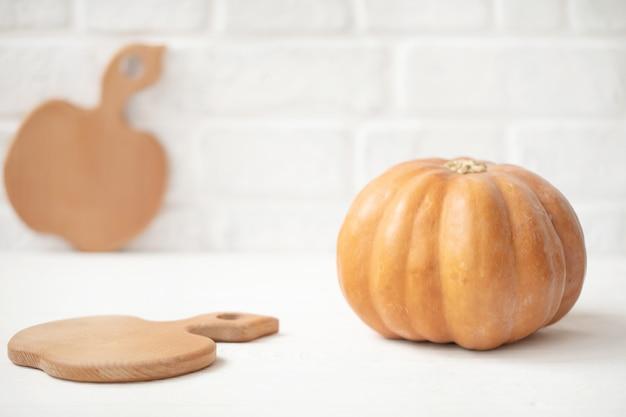 Осенняя тыква с деревянной разделочной доской на стене из белого кирпича