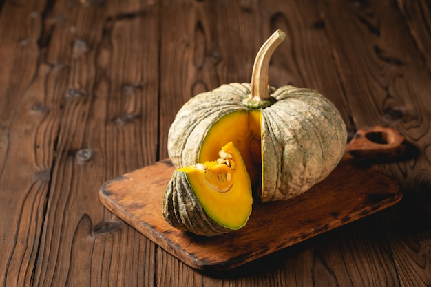 Autumn pumpkin on wooden table.