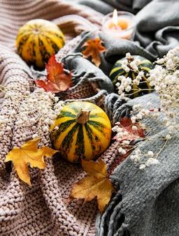 Осенние тыквы, вязаный шарф, кленовые листья и свеча на столе