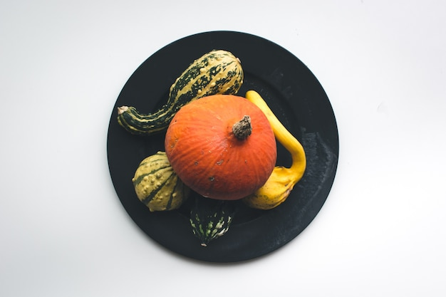 Autumn pumpkins on a plate on a white background