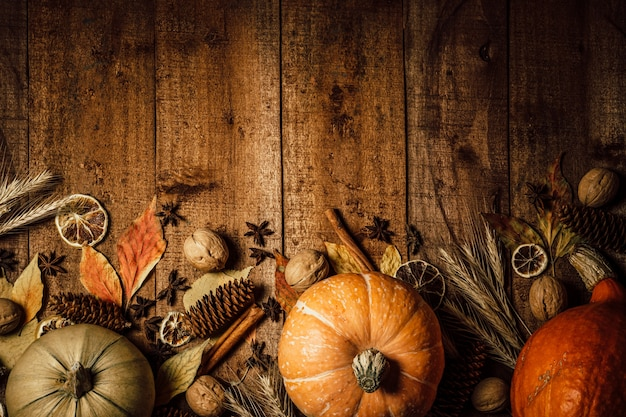 Autumn pumpkins, spikelets and dried flowers on a rough wooden background, top view,