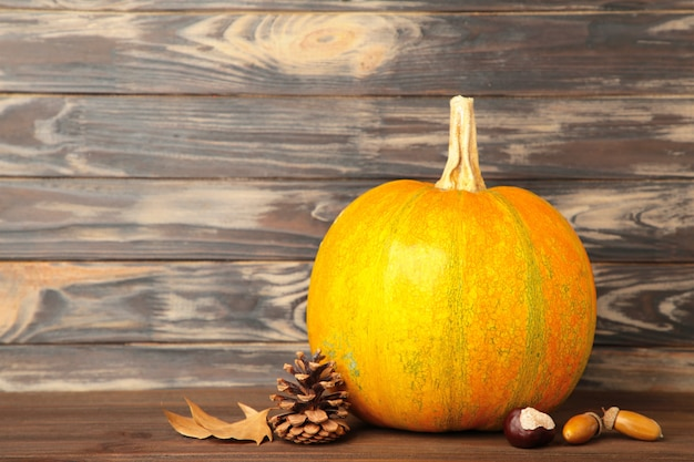 Autumn pumpkins with autumn harvest on brown wooden background. top view