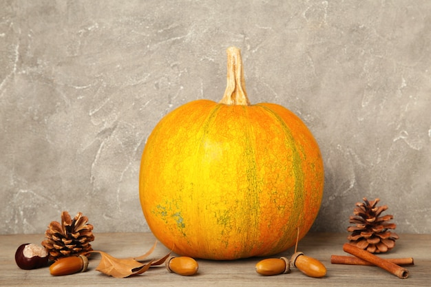Autumn pumpkins with autumn harvest on grey background. top view