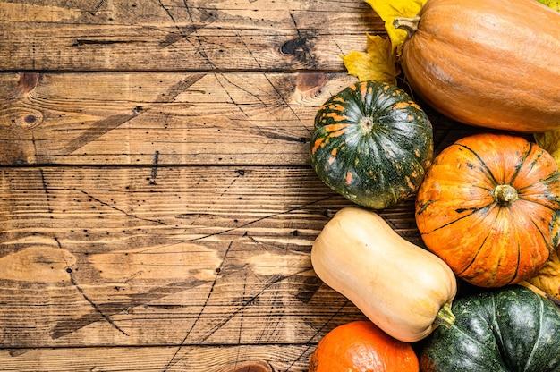 木製のテーブルにカエデの葉と秋のカボチャ