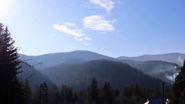 Осенний дождь и туман на горных холмах. туманный осенний лес, покрытый низкими облаками. украина. еловые лесные деревья на холмах гор торчат сквозь утренний туман над осенними пейзажами.