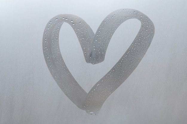 Autumn rain, the inscription on the sweaty glass - love and heart.