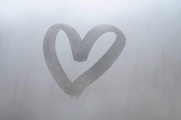Autumn rain, the inscription on the sweaty glass - love and heart