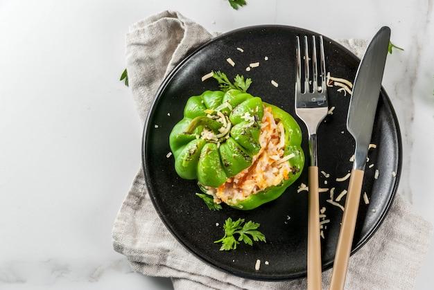 Осенние рецепты. домашний фаршированный сладкий перец с мясным фаршем, морковью, помидорами, зеленью, сыром. на белом мраморном столе, в порционной тарелке, с ножом и вилкой, вид сверху пространства для копирования