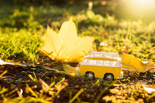 Autumn retro yellow van bus on autumn maple leaf. funny retro toy car. autumn travel and vacation concept