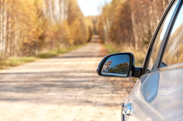 Осенняя дорога в лес сторона машины с зеркалом копирование пространства