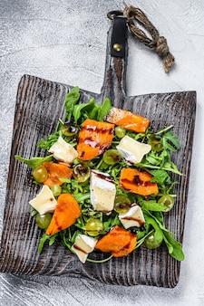 焼きかぼちゃとブリーチーズの秋のサラダ。健康的なビーガンフードのコンセプト。白色の背景。上面図。