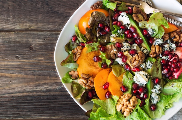 Autumn salad with persimmon pomegranate blue cheese and walnuts on rustic wooden background