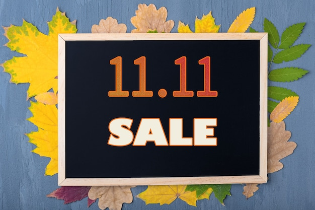 秋のセールのコンセプト。ブラックフライデーのコンセプト。日付11月11日。秋の販売カレンダー。木製の青い背景に紅葉と背景に11.11saleの碑文が付いた黒いフレーム。