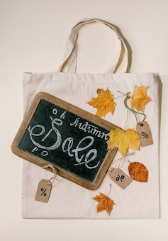 Autumn sale concept. vintage chalkboard with hand written lettering sale, labels with percents, yellow autumn leaves on eco linen shopping bag over beige surface. flat lay.