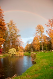 Autumn scene with river and rainbow