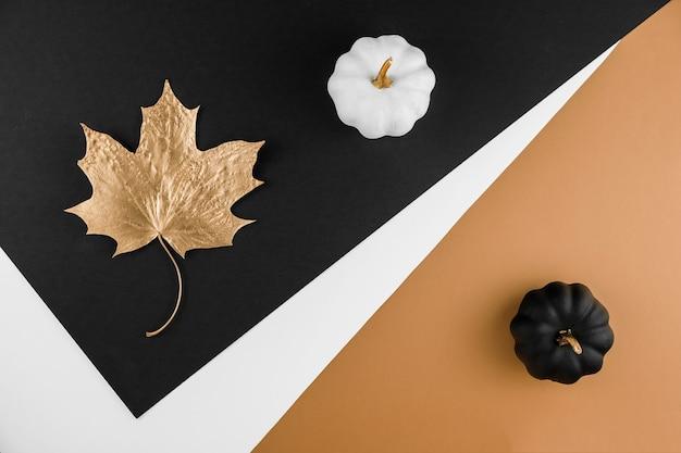 秋の季節の抽象的な背景。秋の黄金の葉とカボチャ