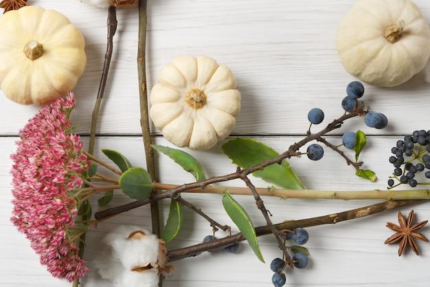秋のシーズン。乾燥した秋の花、カボチャ、枝、紅葉、また綿、クローブ、スローで作られたボーダー。白い木、平面レイアウトのトップビュー