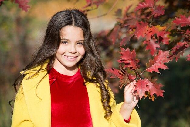 Осенний сезон досуга. атмосфера осени. очаровательная улыбающаяся школьница осенняя листва фон. хорошее настроение. счастливый ребенок. добро пожаловать, октябрь. в единении с природой. маленькая прогулка ребенка в осеннем парке.