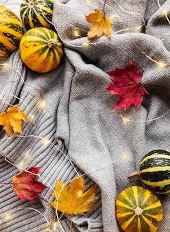 Осенний сезон. праздник благодарения. тыквы и теплый серый свитер с сияющими гирляндами. уютное осеннее настроение. время падения. октябрь и ноябрь. осенние каникулы