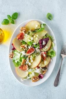 사과, 무화과, 치즈와 함께 가을 계절 샐러드가 접시에 제공됩니다. 위에서보기