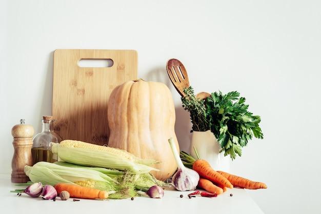 Осенние сезонные овощи и натюрморт кухонной утвари на фоне стены стола. концепция еды благодарения.