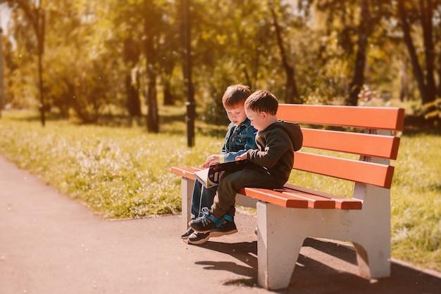 秋9月公園のベンチで本を読んでいる2人の男の子暖かい黄金の秋