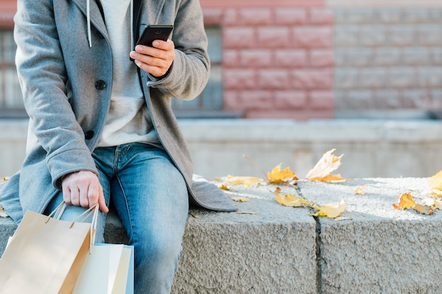 Autumn shopping. cropped shot of man sitting on wall with packages, using smartphone.