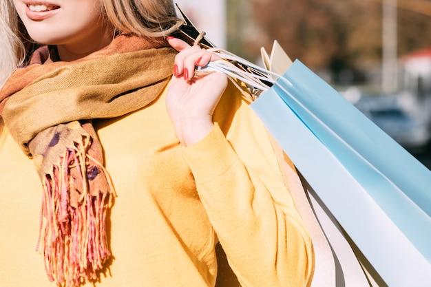 Autumn shopping cropped shot of stylish lady walking with packages, enjoying autumn sunny day