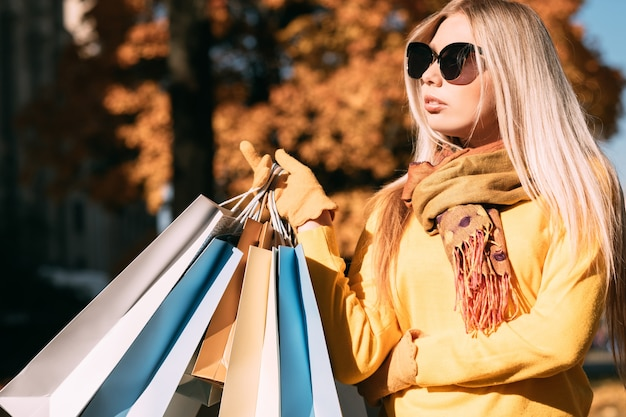 Autumn shopping stylish lady standing with packages, enjoying autumn sunny day