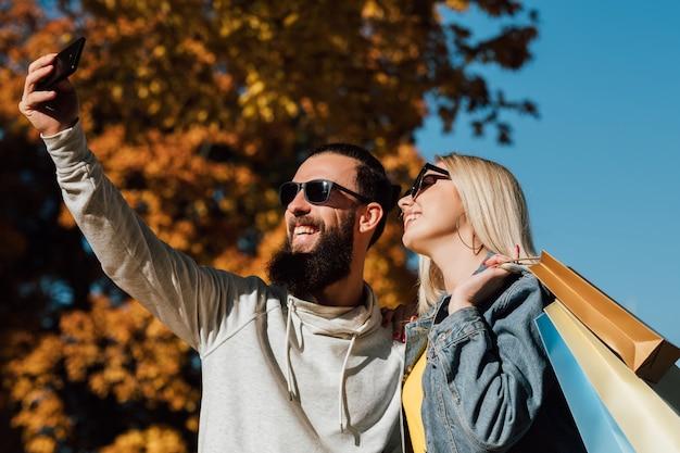 Autumn shopping travel couple taking selfie on smartphone