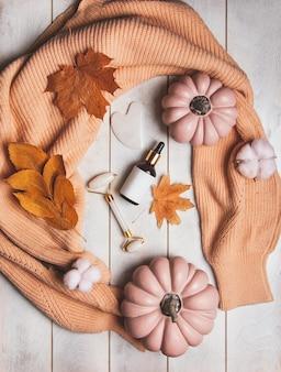 Осенние средства по уходу за кожей - флакон косметики, нефритовый массажер, гуаша, осенние листья, тыквы, вязаный свитер