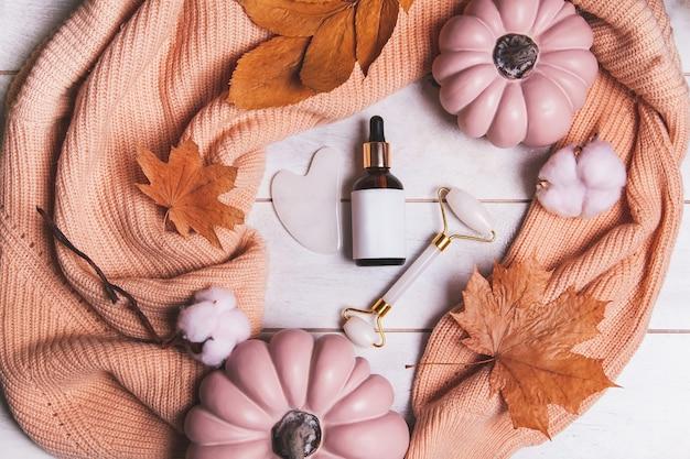 秋のスキンケア製品-化粧品のモックアップボトル、翡翠マッサージャー、グアシャ、紅葉、カボチャ、ニットセーター。季節の美容ルーチンとオーガニックスキンケアのコンセプト。