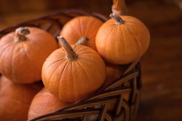 木製のテーブルの上の秋の小さなオレンジ色のカボチャ、収穫、ハロウィーンのシンボル。