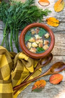 야채와 나무 배경에 크루 통의가 수프.