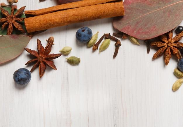 グリューワインの背景の秋のスパイス。乾燥した秋の葉とハーブと調味料で作られたフレームは、シナモン、カルダモン、クローブ、アニス、スローなど。白い木、平面レイアウトのトップビュー
